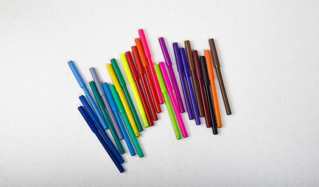 Molte matite colorate, pennarelli, penne, sfondo bianco, pennarelli colorati di giallo, blu, rosso.