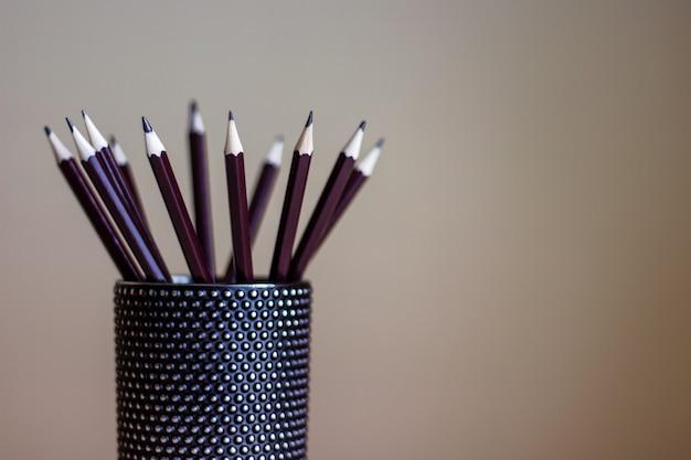 Molte matite di grafite in piedi in un contenitore di vetro nero