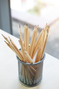 Molte matite marroni sono in scatola d'acciaio sulla scrivania in ufficio moderno