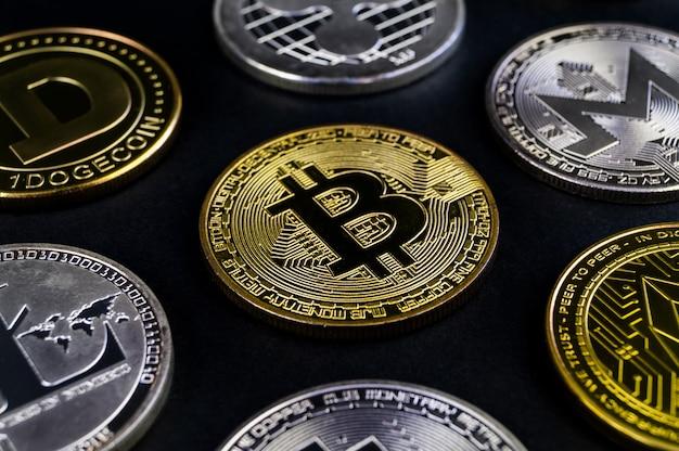 Molte monete di criptovaluta giacciono su una superficie scura