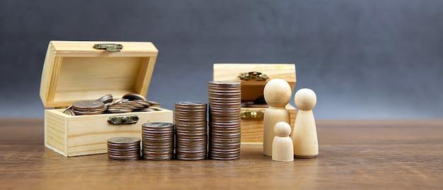 Molte monete sono impilate a forma di grafico con icone familiari per risparmiare denaro.