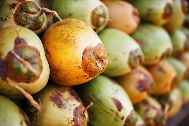 Molte noci di cocco verdi fresche allineate con una pila. bancarelle del primo piano
