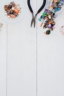 Molte perle colorate e pinza sulla scrivania in legno