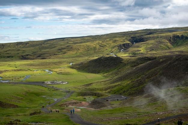 Molte persone camminano lungo uno stretto sentiero in una terra verde circondata da verdi colline