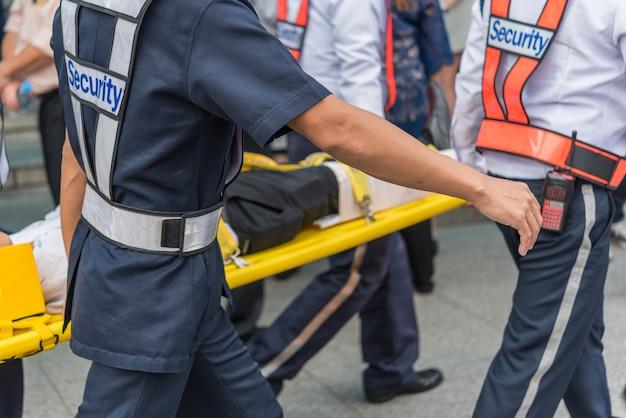 Molte persone che lavorano preparano per un'esercitazione antincendio o altro disastro spostando il paziente infortunato