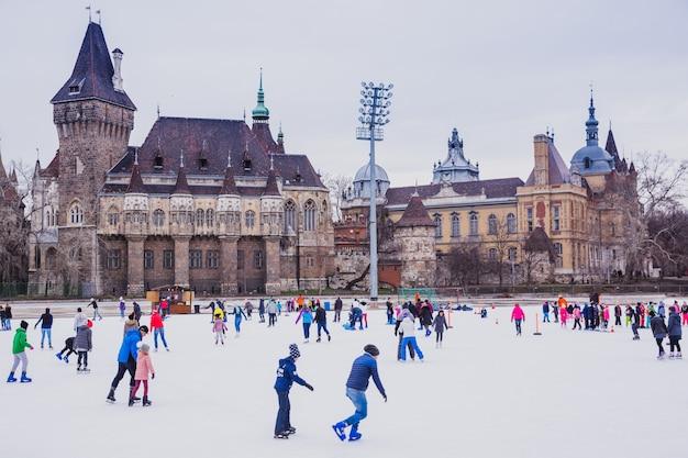 Molte persone trascorrono le loro vacanze pattinando nella pista di pattinaggio del parco cittadino nella parte anteriore di budapestin del castello vajdahunyad, ungheria