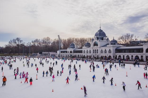 Molte persone trascorrono le loro vacanze pattinando nella pista di pattinaggio di park city a budapest, in ungheria