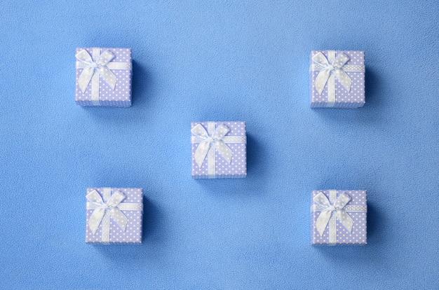 Molte piccole scatole regalo in colore blu con un piccolo fiocco giace su una coperta