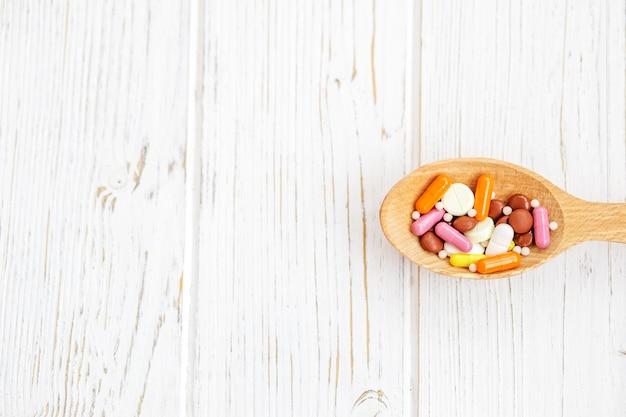 Molte pillole in un cucchiaio di legno.