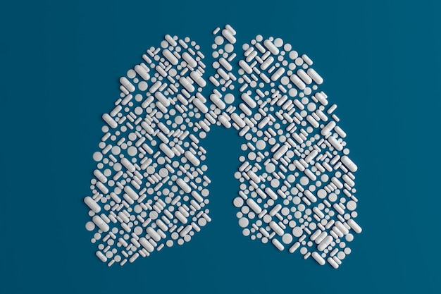 Molte pillole sparse su un blu a forma di polmone