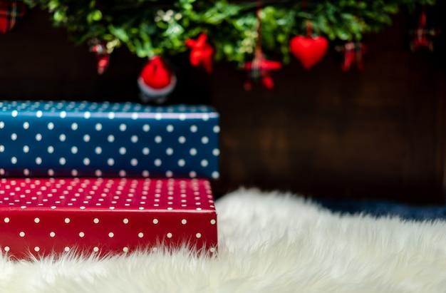 Molte scatole regalo colorate di carta presente posate su un soffice tappeto bianco all'estremità del letto.