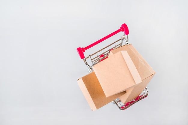 Molte scatole su un primo piano bianco del fondo. carrello in miniatura e copia spazio.