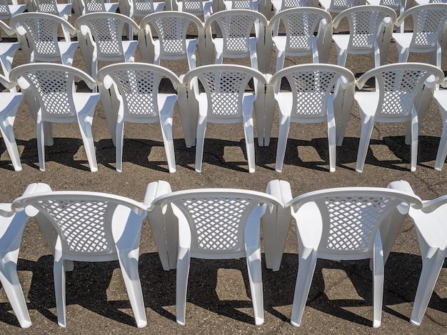 Molte sedie bianche in fila. sedie di plastica senza persone. preparazione per l'evento