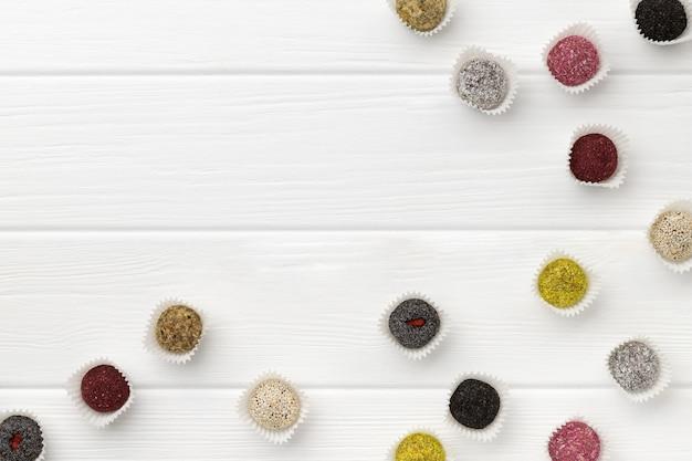 Molte sfere variopinte di energia delle caramelle del vegano sulla tabella di legno bianca
