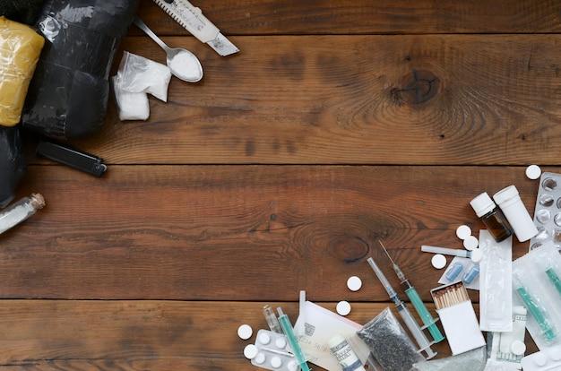 Molte sostanze stupefacenti e dispositivi per la preparazione di droghe su un vecchio tavolo di legno