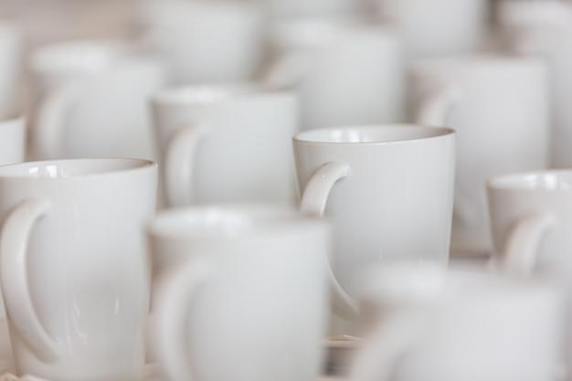 Molte tazze di caffè bianco sono poste sul tavolo.