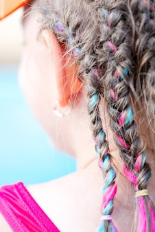 Molte trecce colorate intrecciate sulla testa di una ragazza