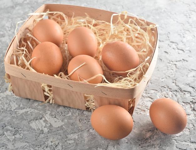 Molte uova di gallina in un cestino con paglia su una superficie di calcestruzzo grigia.
