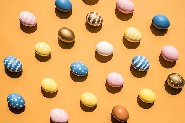 Molte uova di pasqua colorate sparse sul tavolo arancione