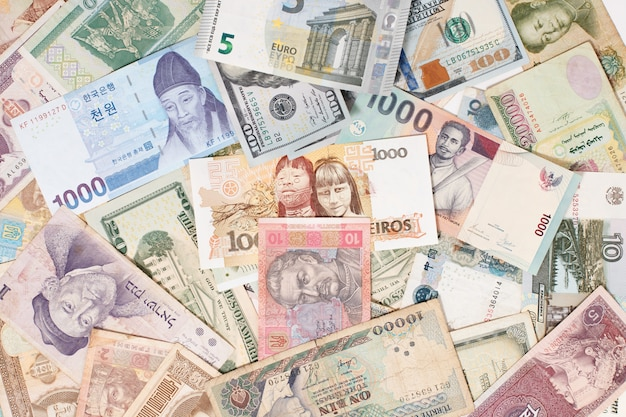 Molte valute diverse come denaro globale concetto di sfondo colorato
