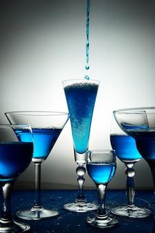 Molti bicchieri con champagne blu o cocktail.