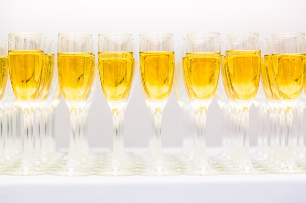 Molti bicchieri con champagne o vino bianco di fila