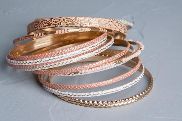 Molti braccialetti su grigio