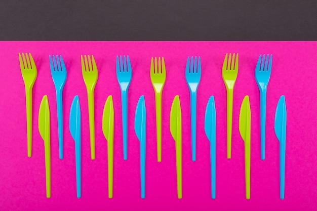 Molti coltelli di plastica di colore su un luminoso