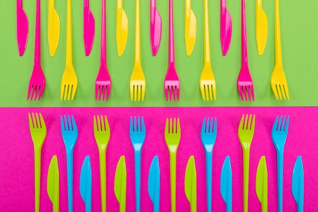 Molti coltelli di plastica di colore su uno sfondo luminoso
