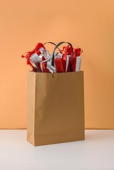 Molti confezione regalo con fiocco in nastro rosso nel sacchetto della spesa di carta marrone. concetti regalo di natale o capodanno