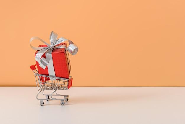 Molti contenitore di regalo con l'arco del nastro rosso e carrello o carrello sulla tavola bianca e sul fondo arancio pastello