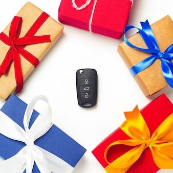 Molti contenitori di regalo e chiavi dell'automobile nel mezzo su un fondo bianco.