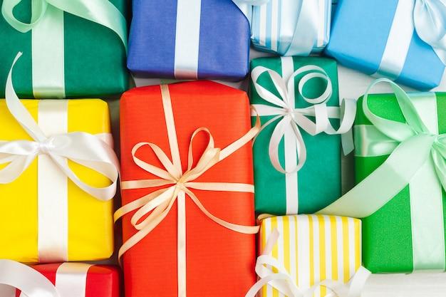 Molti contenitori di regalo variopinti con il fondo dei nastri