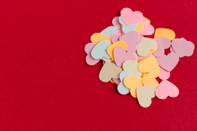 Molti coriandoli a forma di cuore di carta colorata su sfondo rosa o rosso.