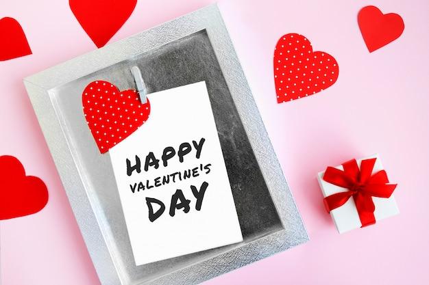 Molti cuori rossi, una cornice con una molletta e la scritta san valentino.