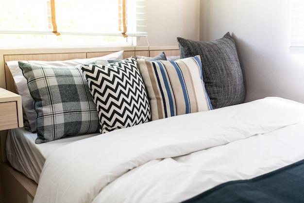 Molti cuscini sul letto bianco