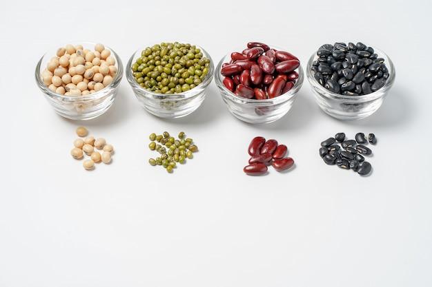 Molti dadi e semi di sesamo su fondo bianco.