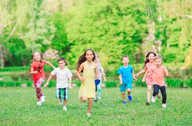 Molti diversi bambini, ragazzi e ragazze che corrono nel parco in giornata di sole estivo in abbigliamento casual