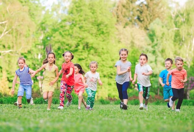 Molti diversi bambini, ragazzi e ragazze che corrono nel parco sulla soleggiata giornata estiva in abiti casual