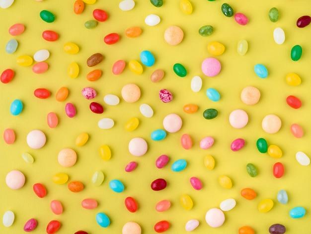 Molti dolci colorati sparsi, caramelle, lecca-lecca su sfondo giallo brillante, vista dall'alto