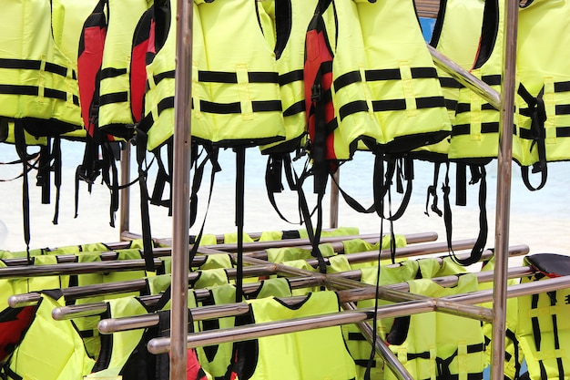 Molti giubbotti di salvataggio gialli luminosi che appendono