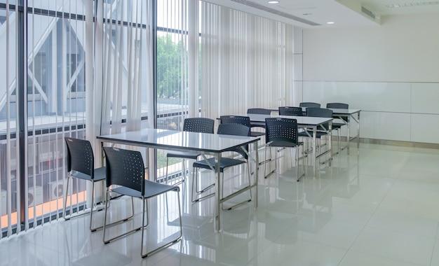 Molti insieme della tabella bianca e delle sedie blu scuro all'ufficio per la riunione dell'impiegato e la pausa caffè