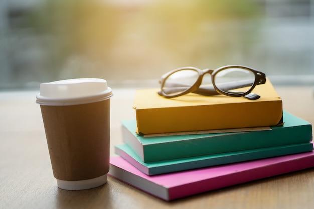 Molti libri sono messi sul tavolo con il caffè.