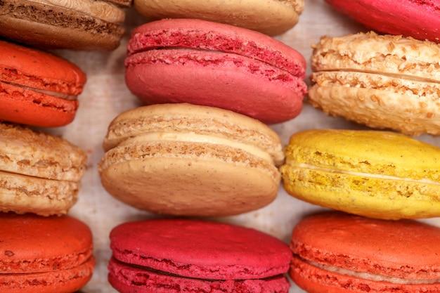 Molti macarons variopinti francesi tradizionali in una scatola, primo piano