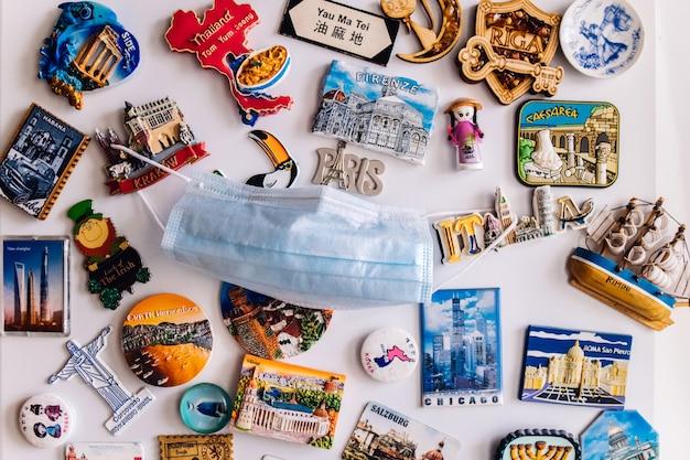 Molti magneti sul frigorifero che mostrano diversi paesi con maschera di protezione per il viso