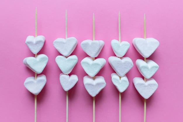 Molti marshmellows a forma di cuore su bastoncini di legno