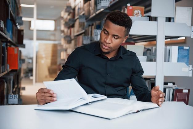 Molti materiali. uomo afroamericano seduto in biblioteca e alla ricerca di alcune informazioni nei libri