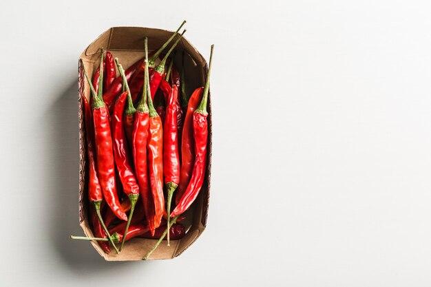 Molti peperoncini caldi in una vista superiore della scatola su un fondo bianco