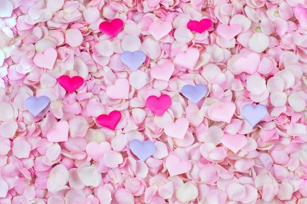 Molti petali di rosa rosa e cuori di raso