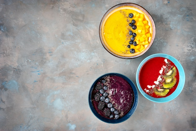 Molti piatti con frullato di frutta colorata visto dall'alto